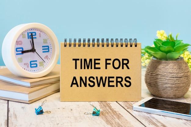 Een bord met het opschrift time for answers op tafel met kantoorbenodigdheden