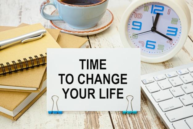 Een bord met het opschrift time to change your life op tafel met kantoorbenodigdheden