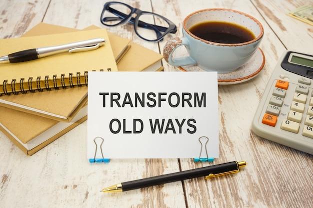 Een bord met het opschrift transform old ways op tafel met kantoorbenodigdheden