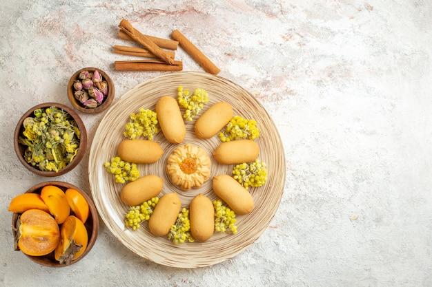 Een bord met koekje en pijpjes kaneel en droge bloemen en palm aan de linkerkant van de grond