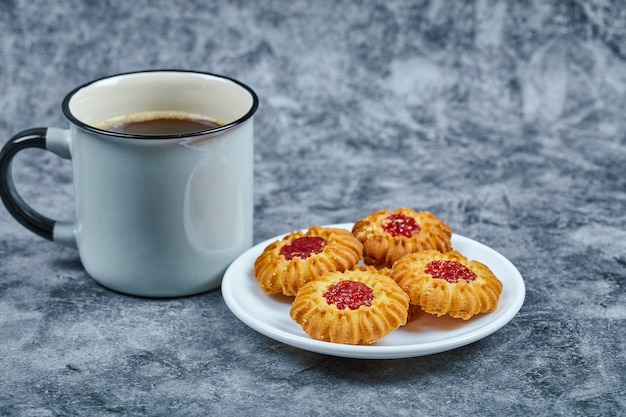 Een bord met koekjes en koffie op marmeren tafel.
