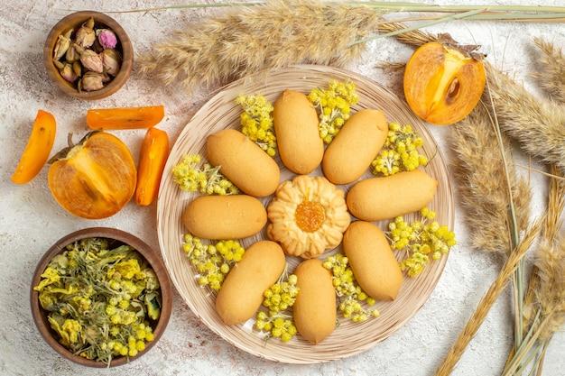 Een bord met koekjes en kommen met droge bloemen en emmers en palmen op marmer
