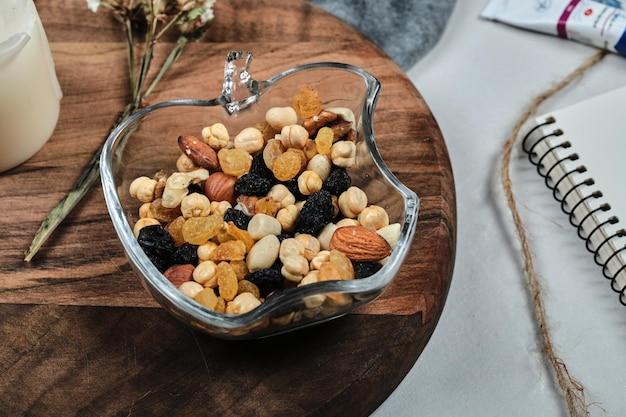 Een bord met noten met kaars, bloem, papier en buizen op een houten bord.