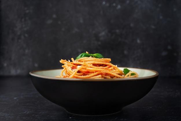 Een bord met pasta in tomatensaus op zwarte achtergrond