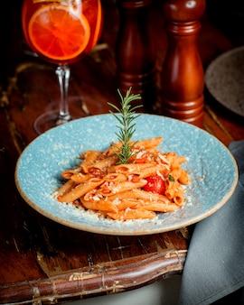 Een bord met penne-pasta met tomatensaus en parmezaanse kaas