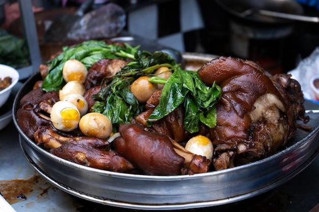 Een bord met producten voor soep. gerookt vlees en gekookte eieren met groenen. ingrediënten voor soep