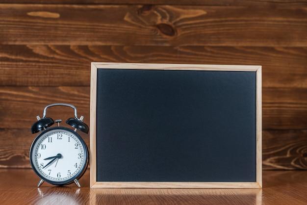 Een bord met ruimte voor tekst en een wekker op een houten ruimte.
