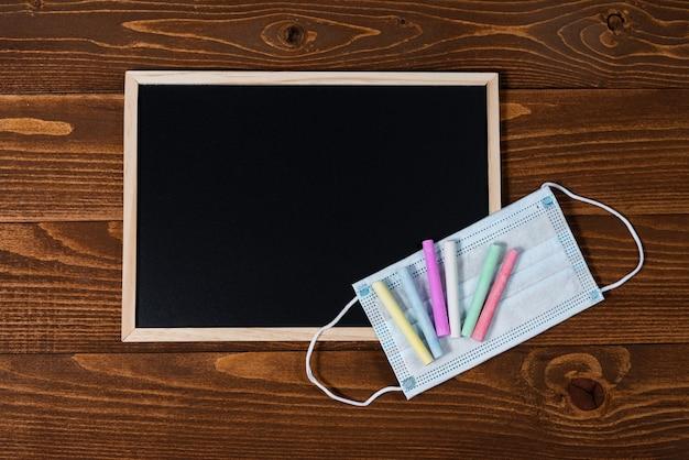 Een bord met ruimte voor tekst, set kleurpotloden en een beschermend masker op een houten