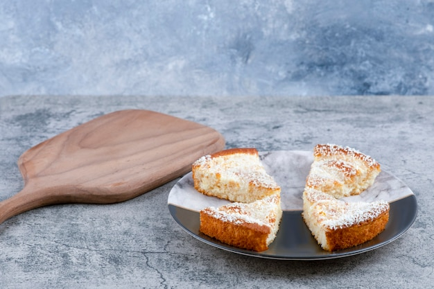 Een bord met stukjes heerlijke cake op een marmeren tafel.