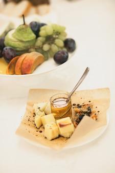 Een bord met stukjes kaas van verschillende soorten en honing