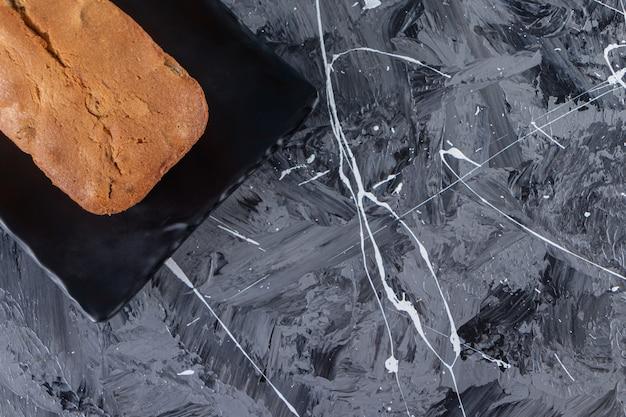 Een bord met vers gebakken rozijnenbrood op een marmeren achtergrond.