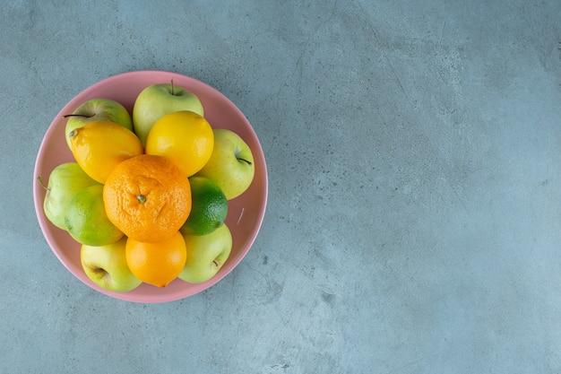 Een bord met verschillende soorten fruit, op de marmeren achtergrond. hoge kwaliteit foto