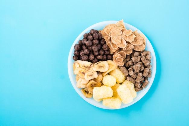 Een bord met verschillende soorten ontbijt en snacks: havermout, ontbijtgranen, chocoladeballen, bananenchips en roggezemelen op een blauwe tafel. bovenaanzicht