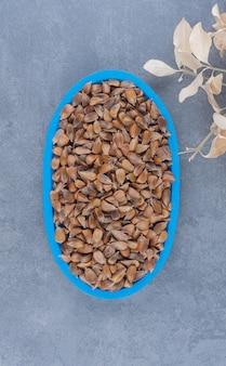 Een bord met zaden naast de bladeren, op de marmeren achtergrond.