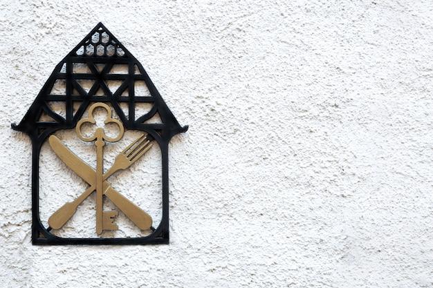 Een bord op de muur met het beeld van het huissleutelmes en de vork.