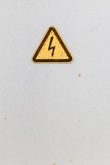 Een bord op een metalen doos over een waarschuwing over het gevaar van elektriciteit