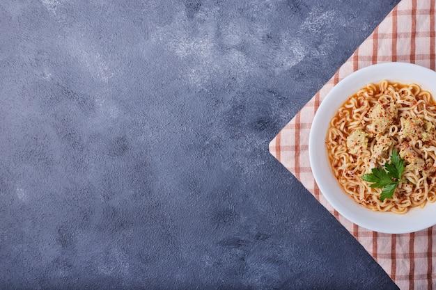 Een bord pasta op blauwe tafel met kruiden.