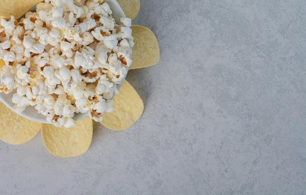 Een bord popcorn omgeven door chips op marmeren oppervlak