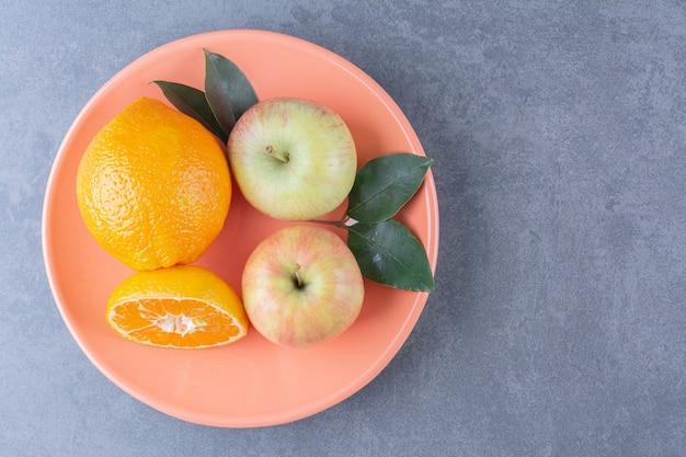 Een bord smakelijke appel en sinaasappels op marmeren tafel.