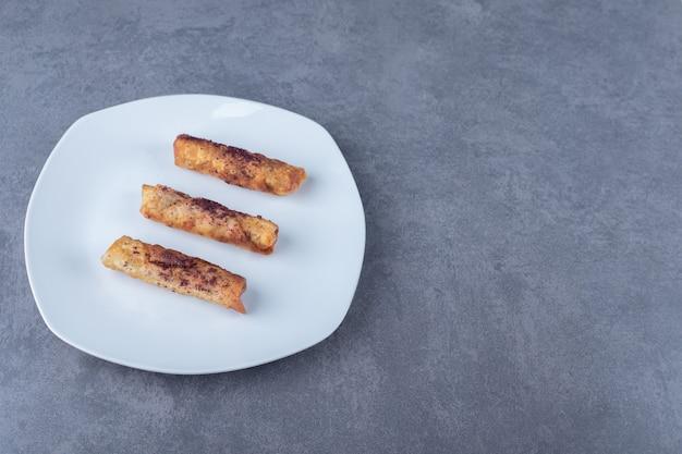 Een bord sumak over vlezige pannenkoeken op de houten plaat op marmeren tafel.