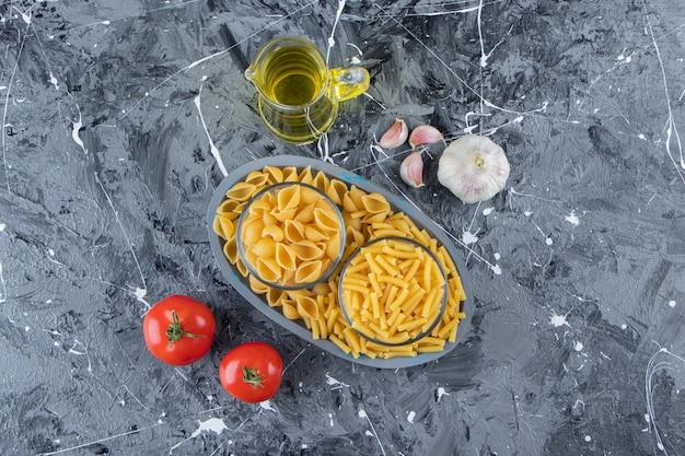 Een bord van twee soorten rauwe macaroni met groenten en olie op een marmeren ondergrond.