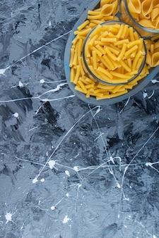Een bord van twee soorten rauwe macaroni op een marmeren achtergrond.