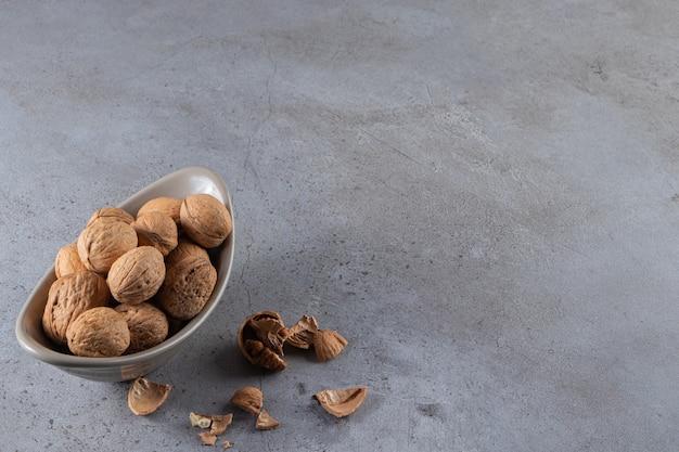 Een bord vol gezonde walnoten geplaatst op stenen achtergrond.