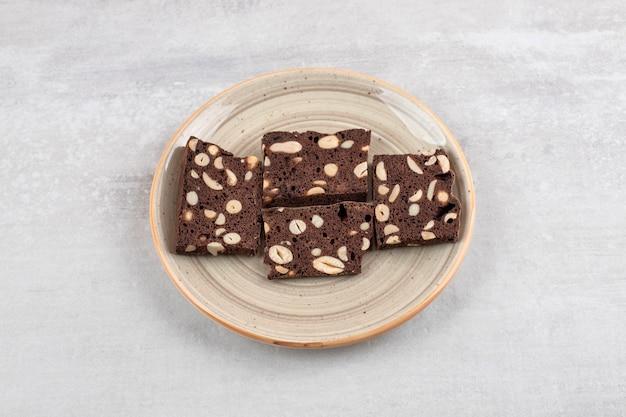Een bord vol met sneetjes bruin brood met noten op een stenen tafel.