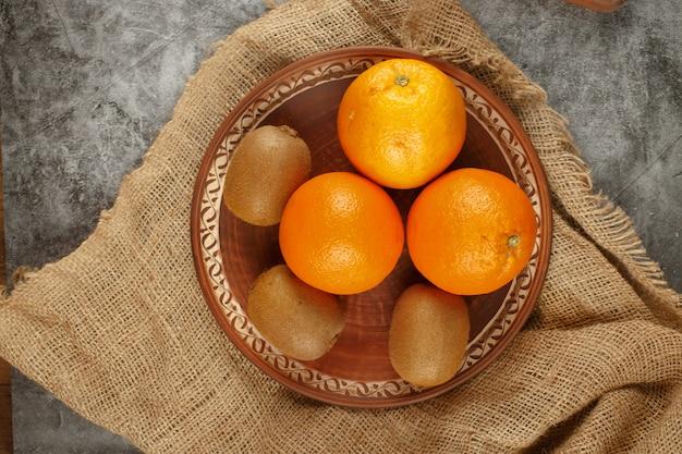 Een bord vol sinaasappels en kiwies. bovenaanzicht