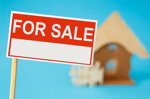 Een bord voor de verkoop van onroerend goed en een huis