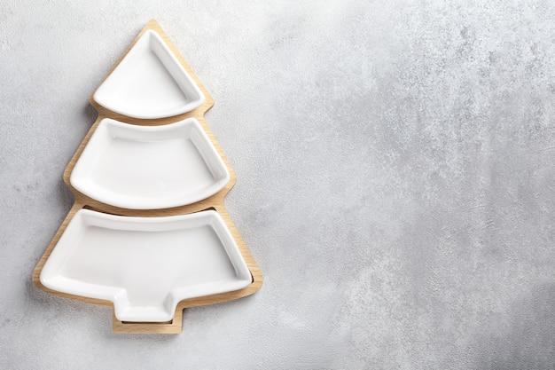 Een bord voor snacks in de vorm van een kerstboom op een lichte achtergrond