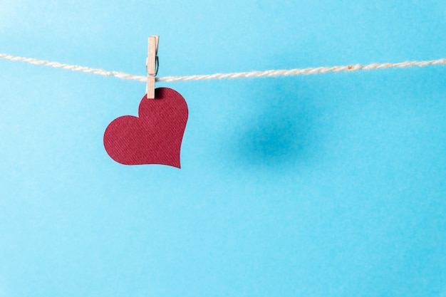 Een bordeauxrode hart opknoping op een touw met een kleine wasknijper op een blauwe achtergrond.