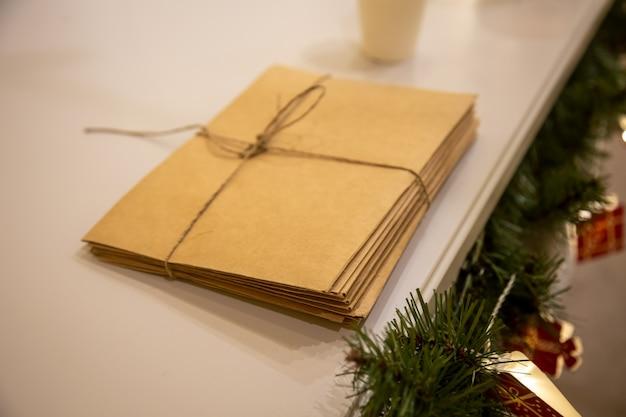 Een bos brieven aan de kerstman gemaakt van ambachtelijk papier vastgebonden met een touw naast kerstversieringen en een kerstboom