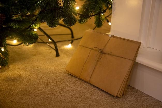 Een bos brieven aan de kerstman gemaakt van kraftpapier, vastgebonden met een touw, ligt naast de kerstboom
