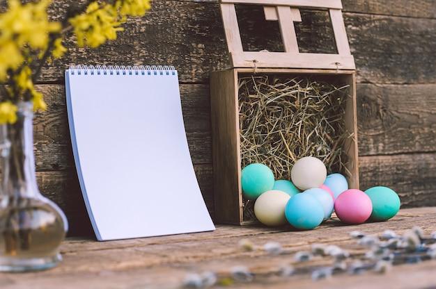 Een bos gekleurde eieren met hooi en een notitieboekje. tegen de achtergrond van een oud bord. concept op het thema van paasdag.