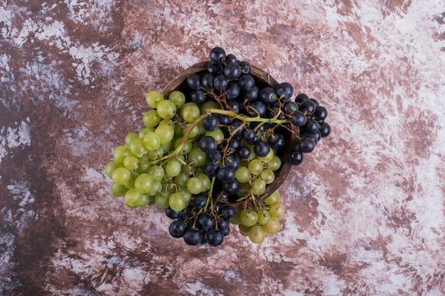 Een bos groene en rode druiven op het marmer