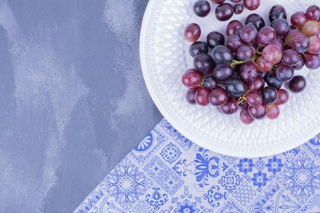 Een bos rode druiven in een witte plaat.