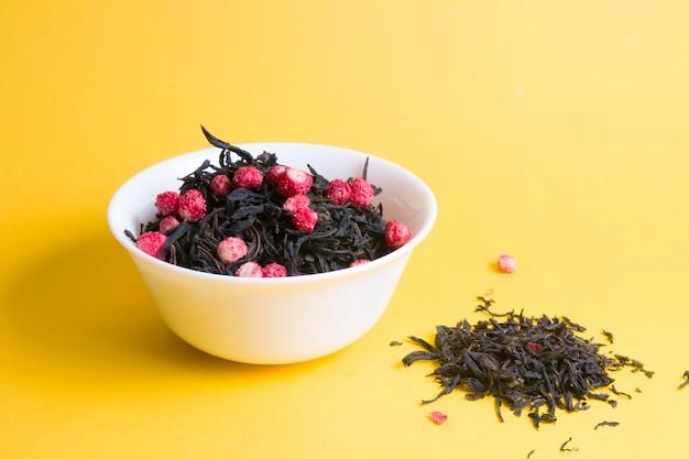 Een bos thee met gedroogde aardbeien in een kleine witte kom op een gele achtergrond, een handvol thee is verspreid op een gele achtergrond
