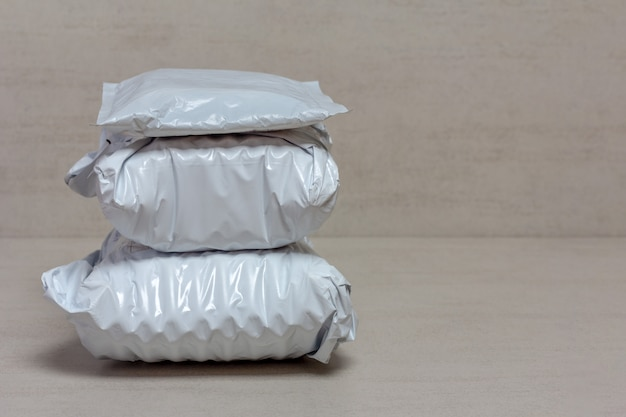 Een bos van grijze postpakketten van chinese winkels sluit omhoog op een grijze achtergrond met exemplaarruimte