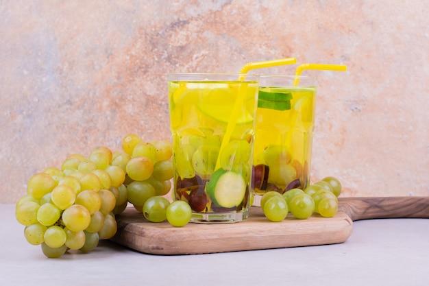 Een bos van groene druiven op een houten bord met twee glazen sap.