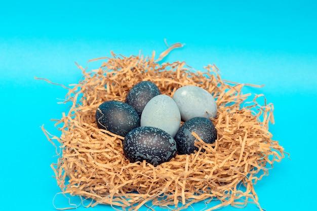 Een bos van mooie ongebruikelijke paaseieren ligt in een nest tegen een blauwe achtergrond