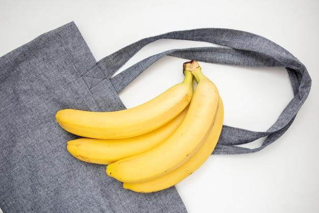 Een bos van rijpe gele bananen op een boodschappentas