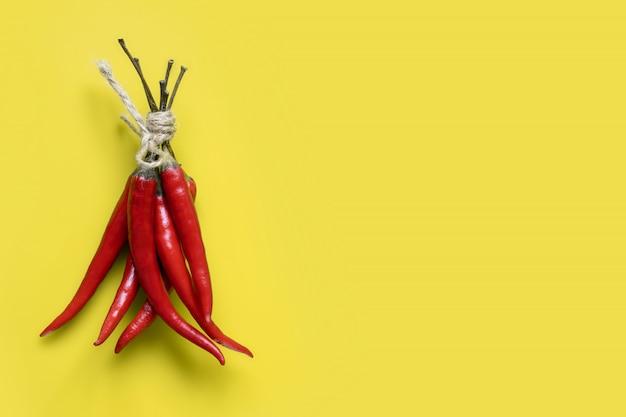 Een bos van rode hete pepers vastgebonden met henneptouw op geel