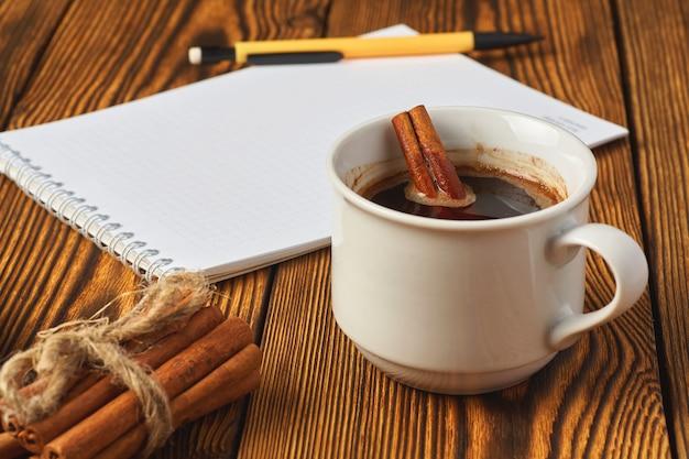 Een bosje kaneel gebreid met een touw, een kopje koffie en een notitieboekje
