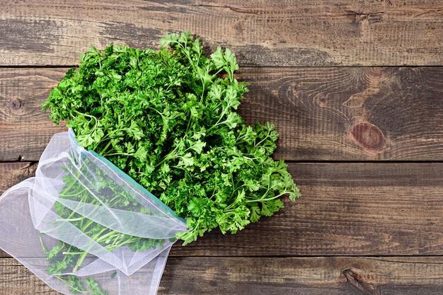 Een bosje vers groen in een milieuvriendelijke herbruikbare tas op een houten achtergrond met een close-up kopie van de ruimte