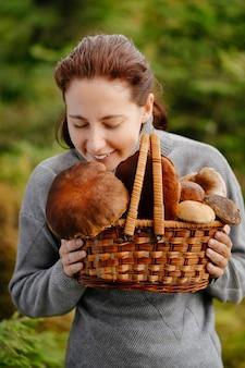 Een boswachtervrouw snuift de verzamelde verse witte en rode paddenstoelen in een mand biologisch voedsel