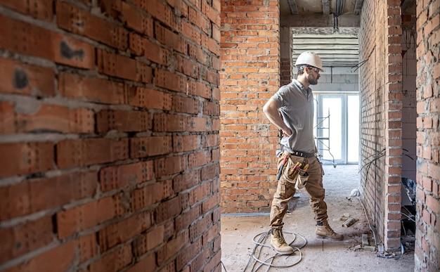 Een bouw elektricien snijdt een spanningskabel tijdens een reparatie.