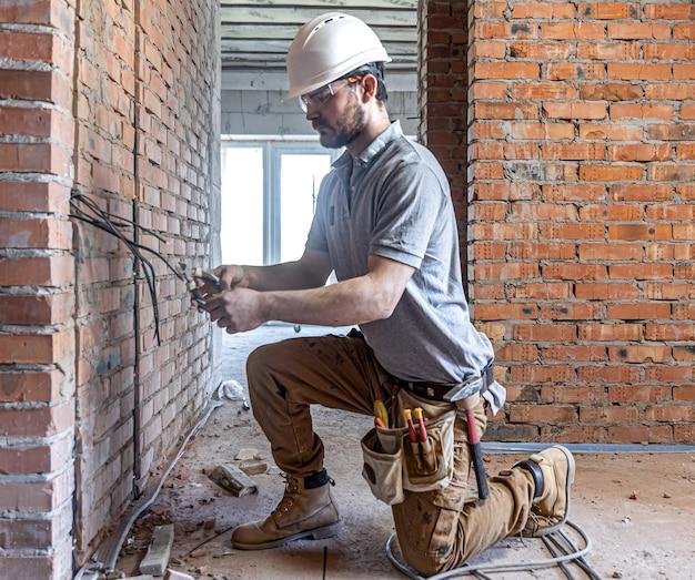 Een bouw-elektricien snijdt een spanningskabel tijdens een reparatie.
