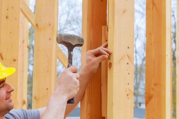 Een bouwdagarbeider die houten stralen vervoert