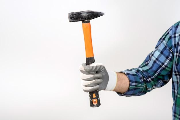 Een bouwer in een beschermende helm houdt een hamer op een witte muur close-up